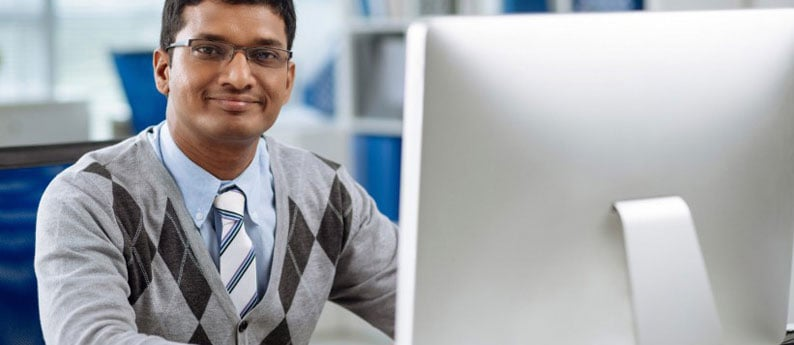 A student taking Online Career Training Programs sitting in front of his computer. He is smiling and looking at the camera.