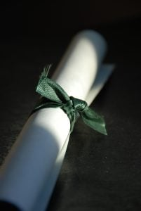 Close up of a rolled-up diploma tied with a green ribbon.