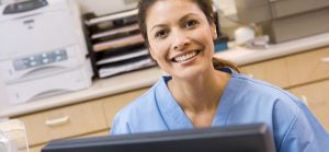Nurse Sitting At A Computer At The Reception Area Of A Hospital Looking At Camera Smiling