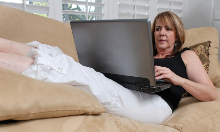 Woman lounging on her couch, laptop in her lap, taking her online courses.