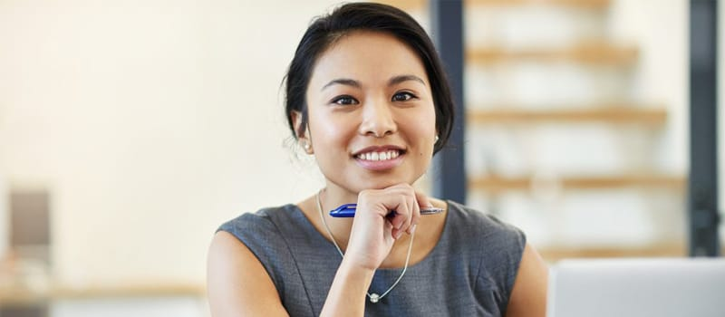 A young Asian woman is sitting in front of a laptop computer smiling, possibly because she's satisfied with her progress in the online courses she's taking in Alberta through the Centre for Distance Education