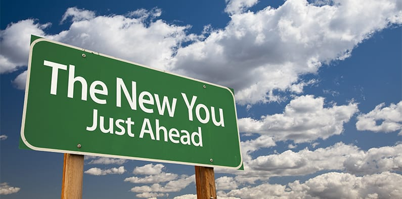 """A sign in the foreground reads """"The New You Just Ahead"""" with a blue sky and puffy white clouds behind it"""
