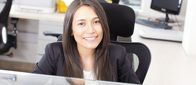 Female Office Administrator sitting at a desk.